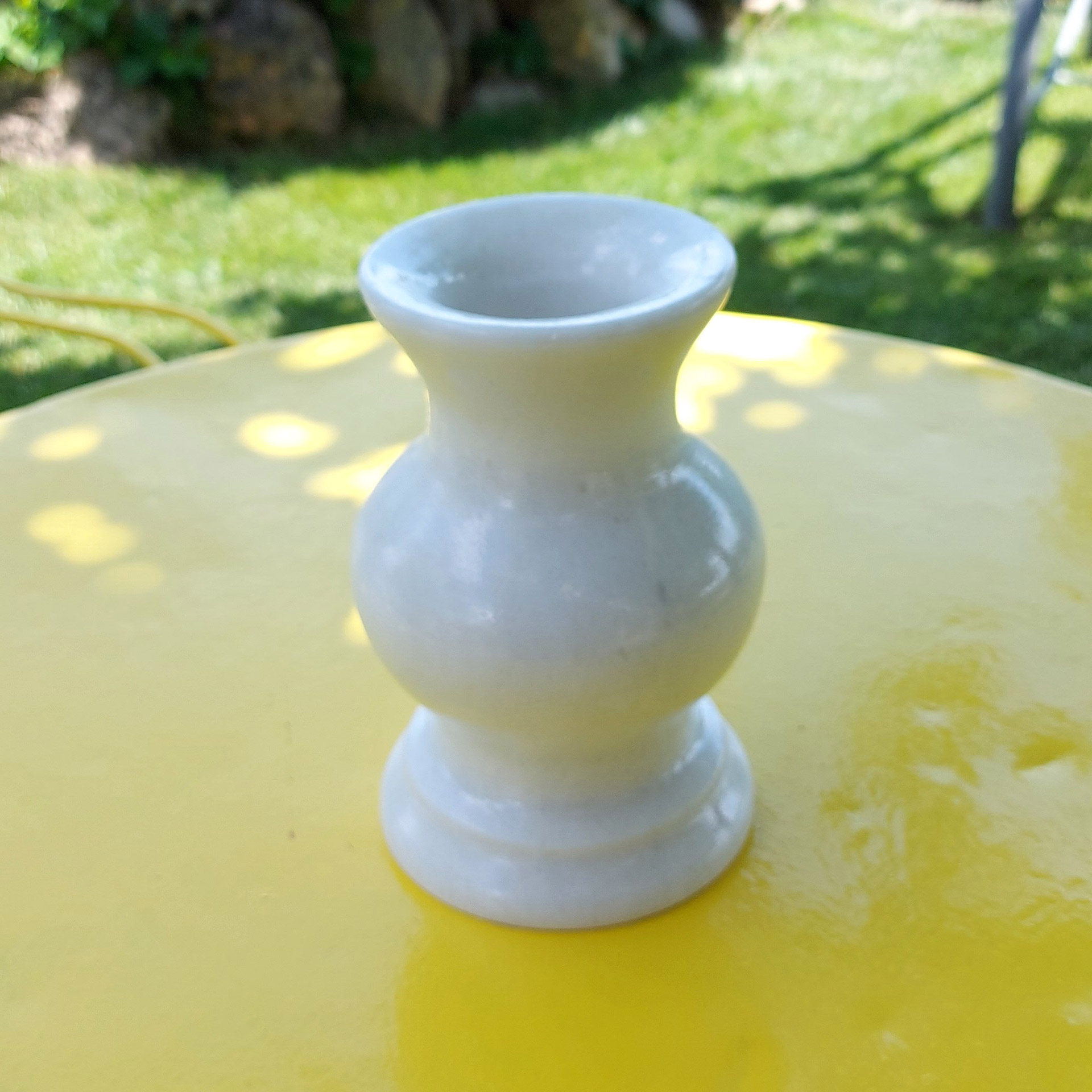 Μαρμάρινο βάζο Αμαρυλλίς σε τραπέζι κήπου